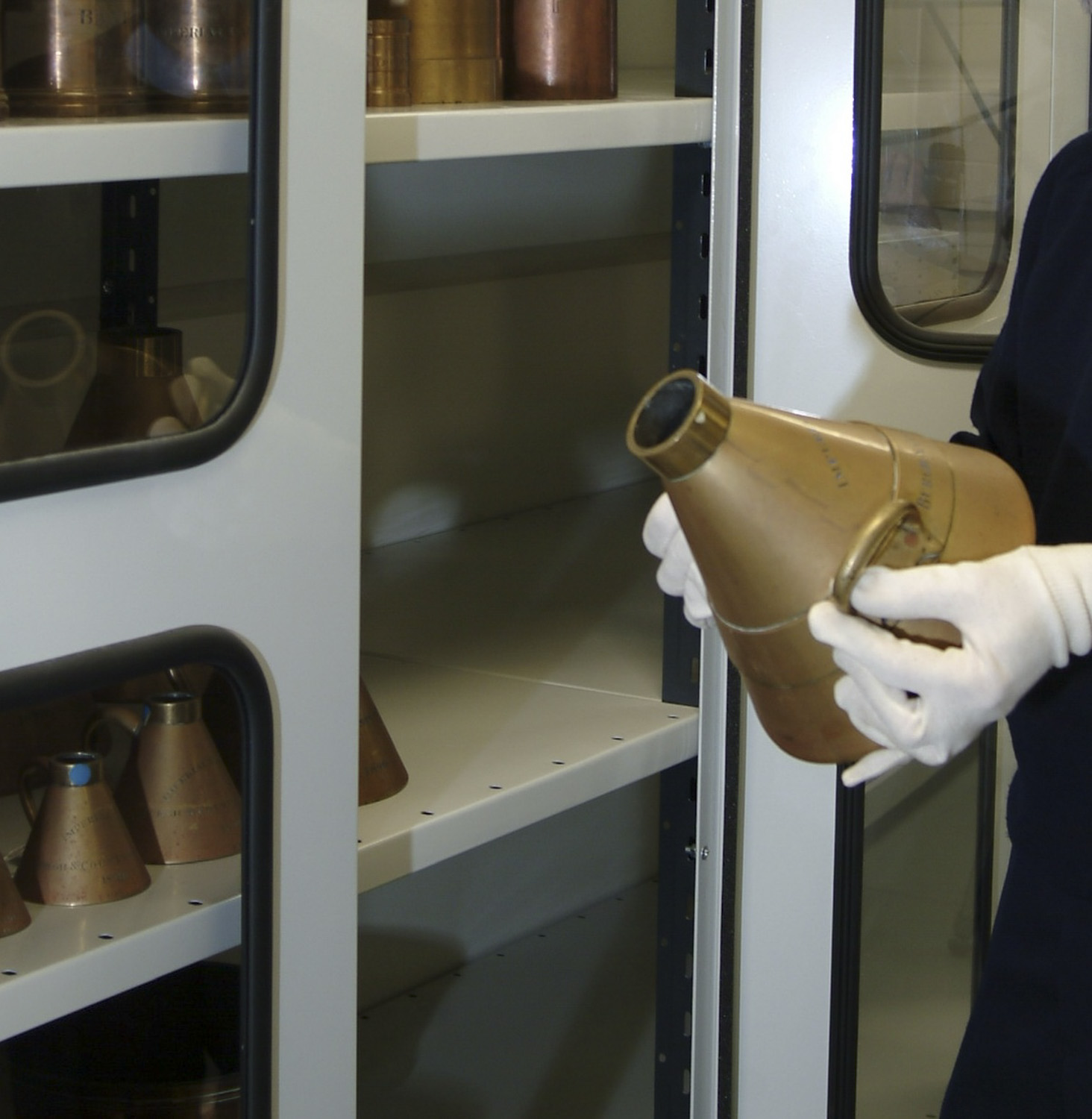 Someones gloved hands holding a brass measure. Shelves in the background.