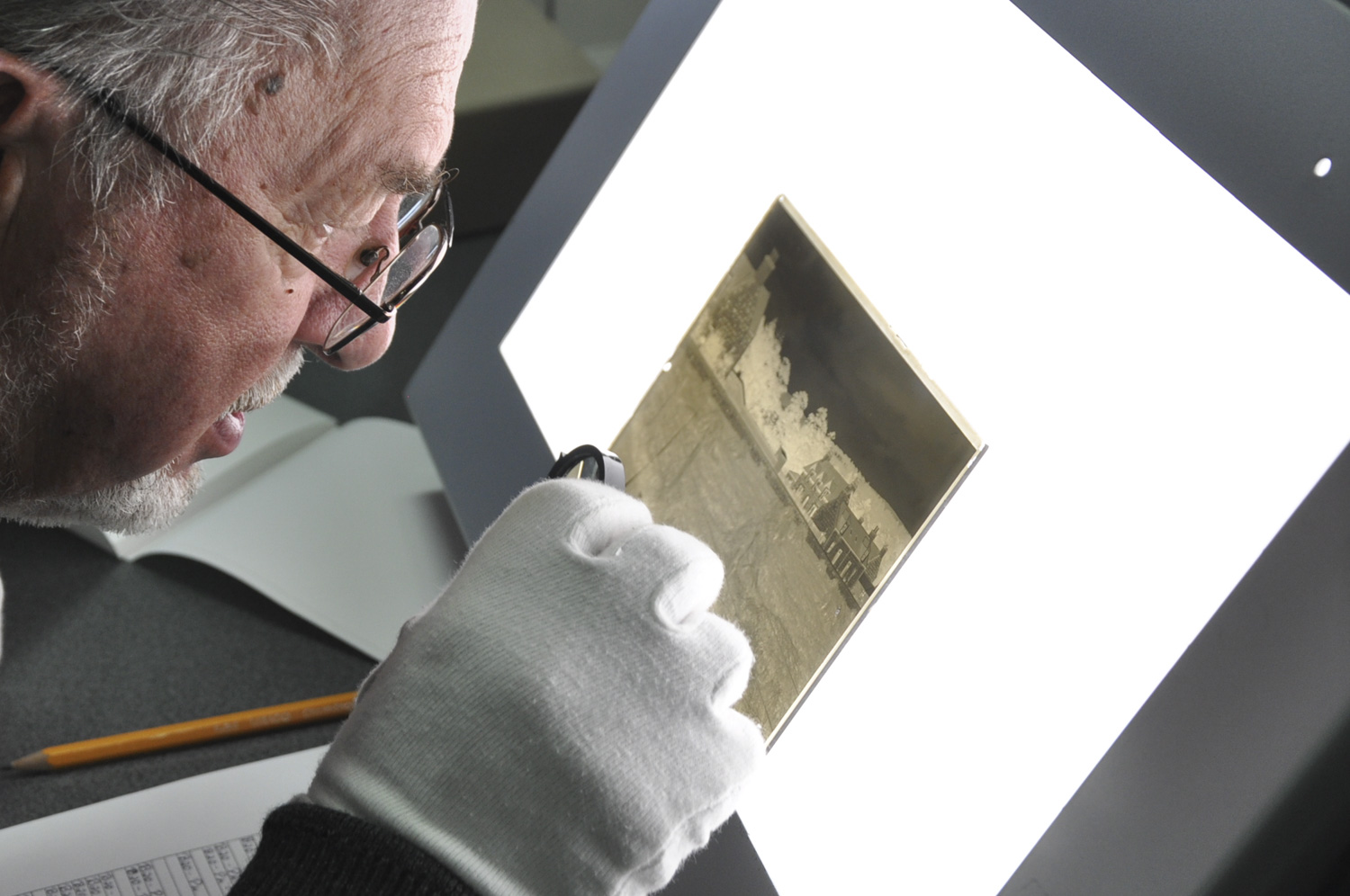 Gentleman looking closely at a glass negative on a lightbox.