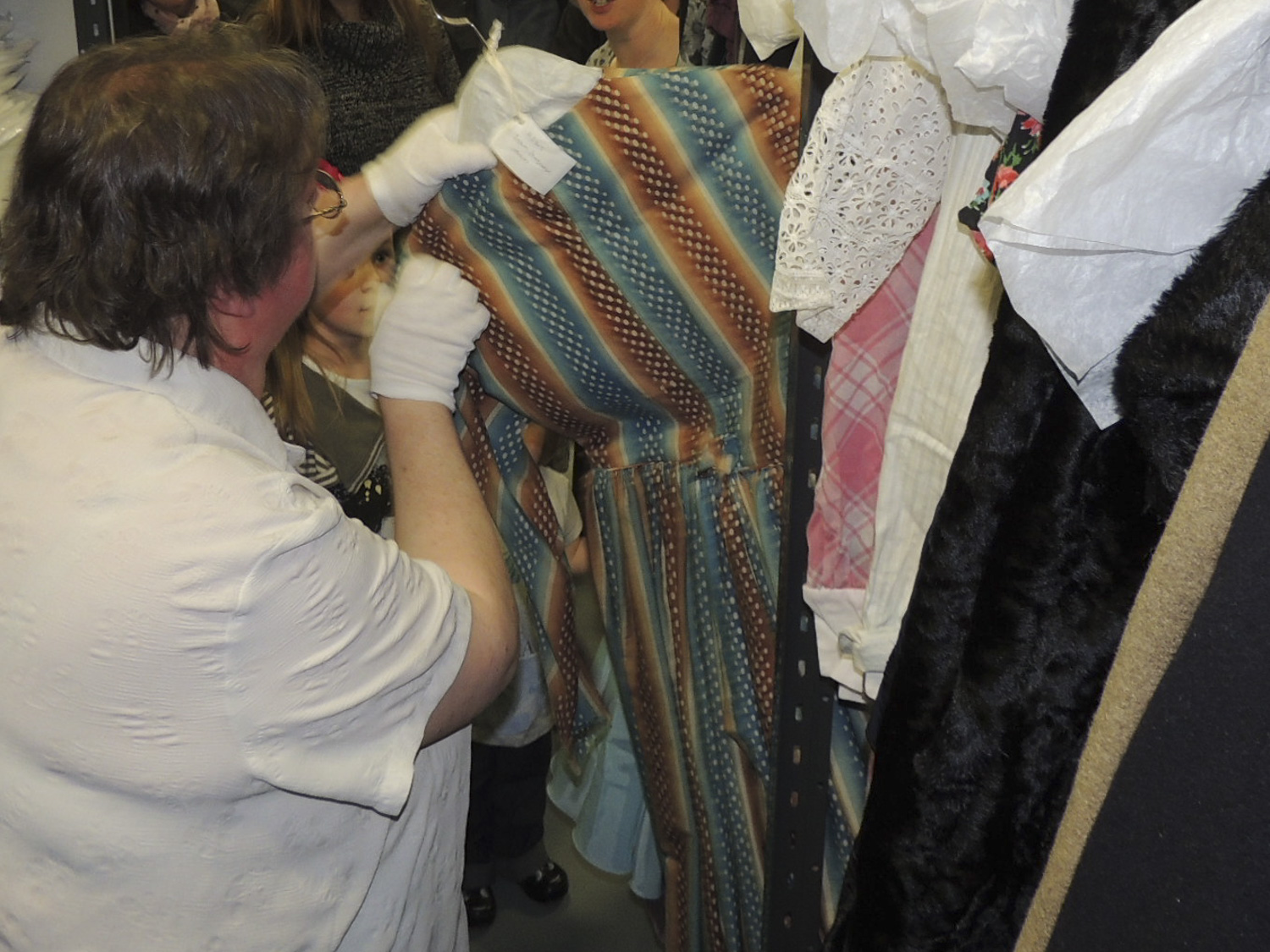 Lady with gloved hands inspecting a dress from the collections.