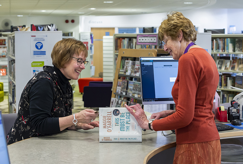librarian issuing book to customer