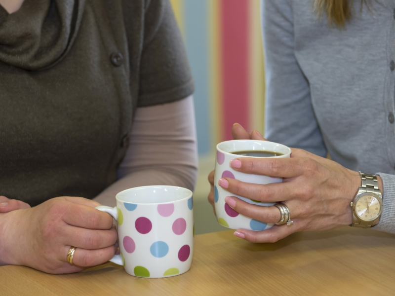 close up of hands holding mugs