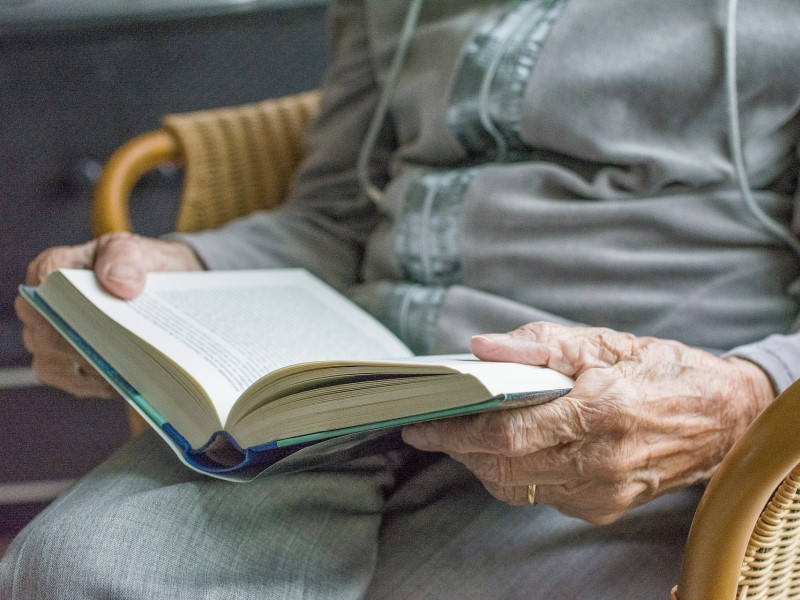 elderly person reading a book