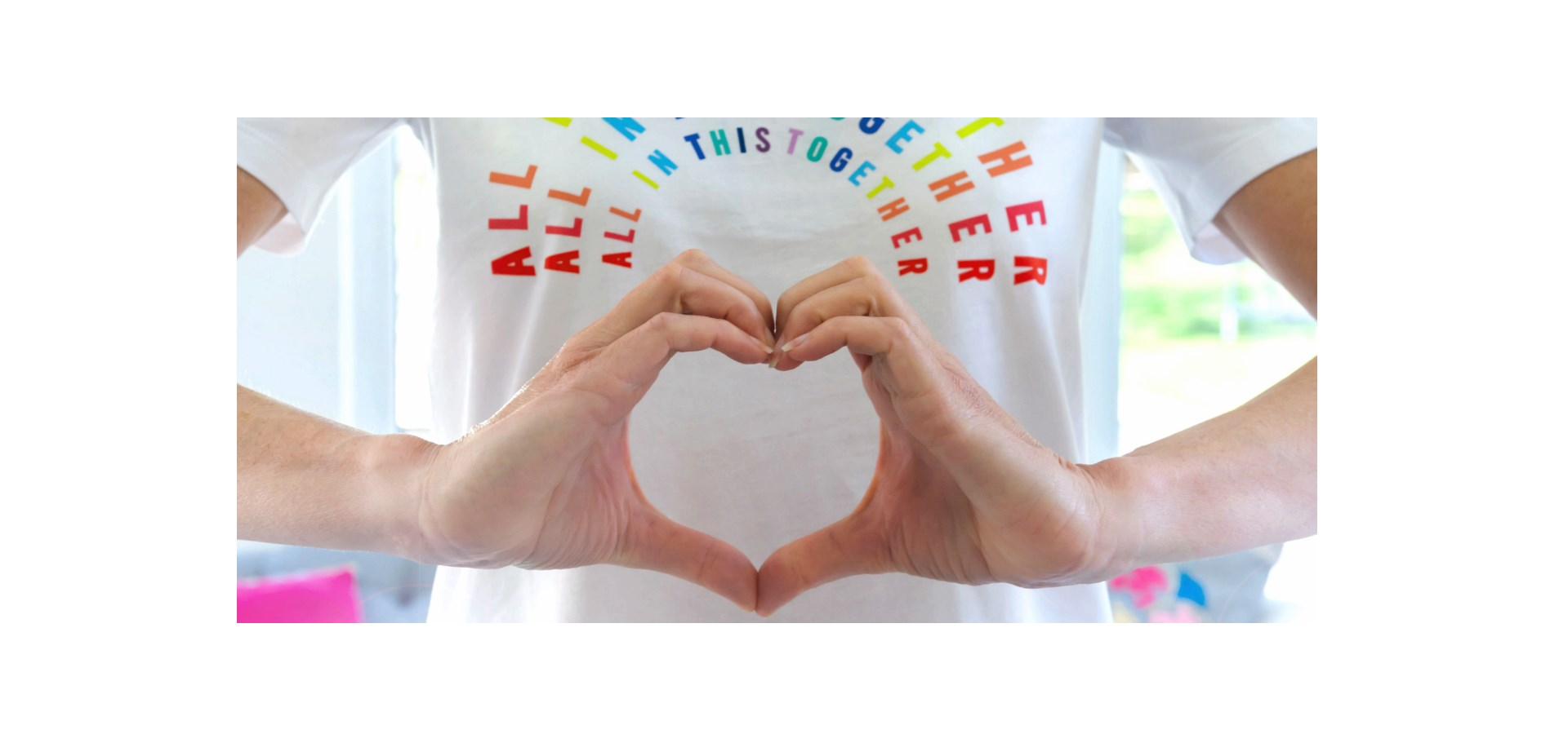 A person making a heart shape with their hands and a printed message on their t shirt - All in this together